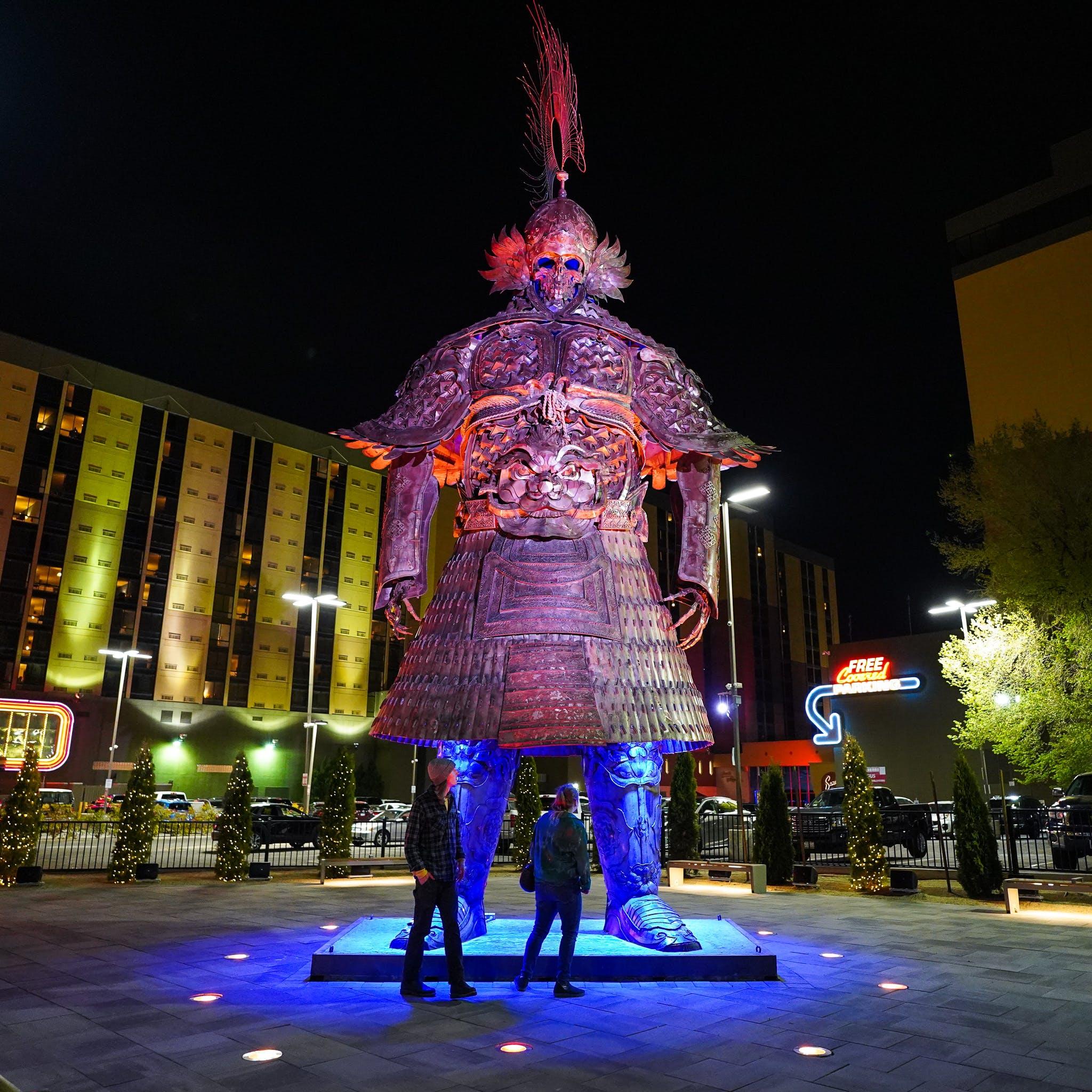 couple looking at giant samurai burning man art on neon line Reno