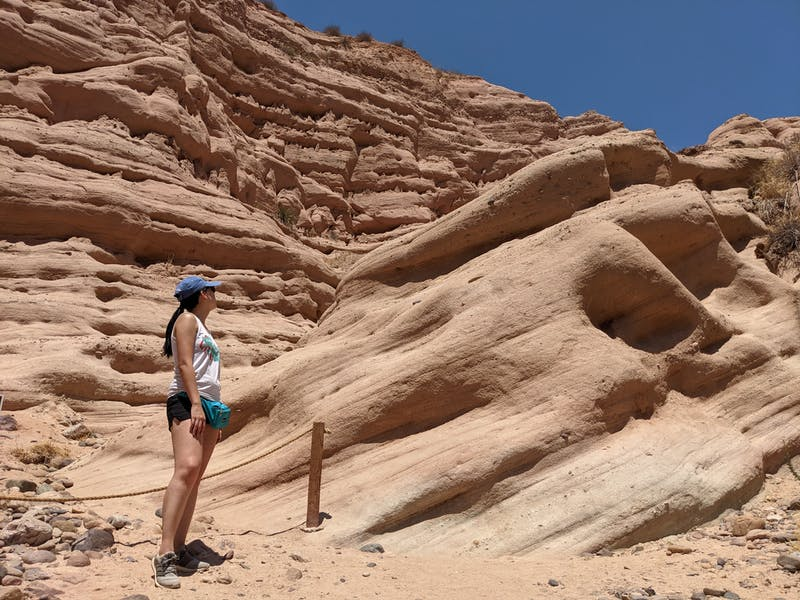 Woman standing and observing the red rock formation at the end of a hiking trail in Whiting Ranch Wilderness Park in Orange County