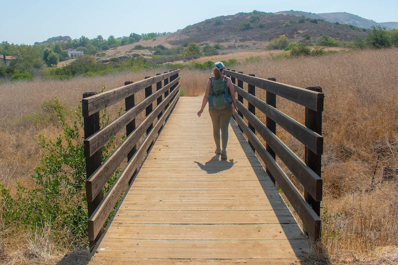 Hiker crossing over a bridge on the trail at Bommer Canyon Open Space Preserve in Orange County