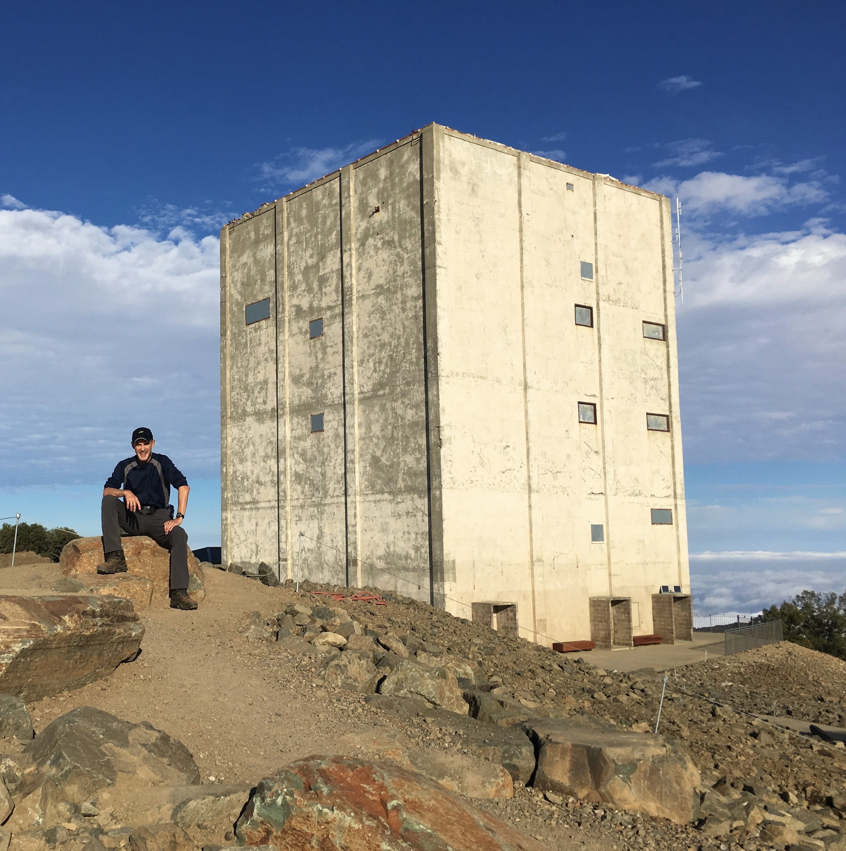 A person sitting in front of The Cube radar tower