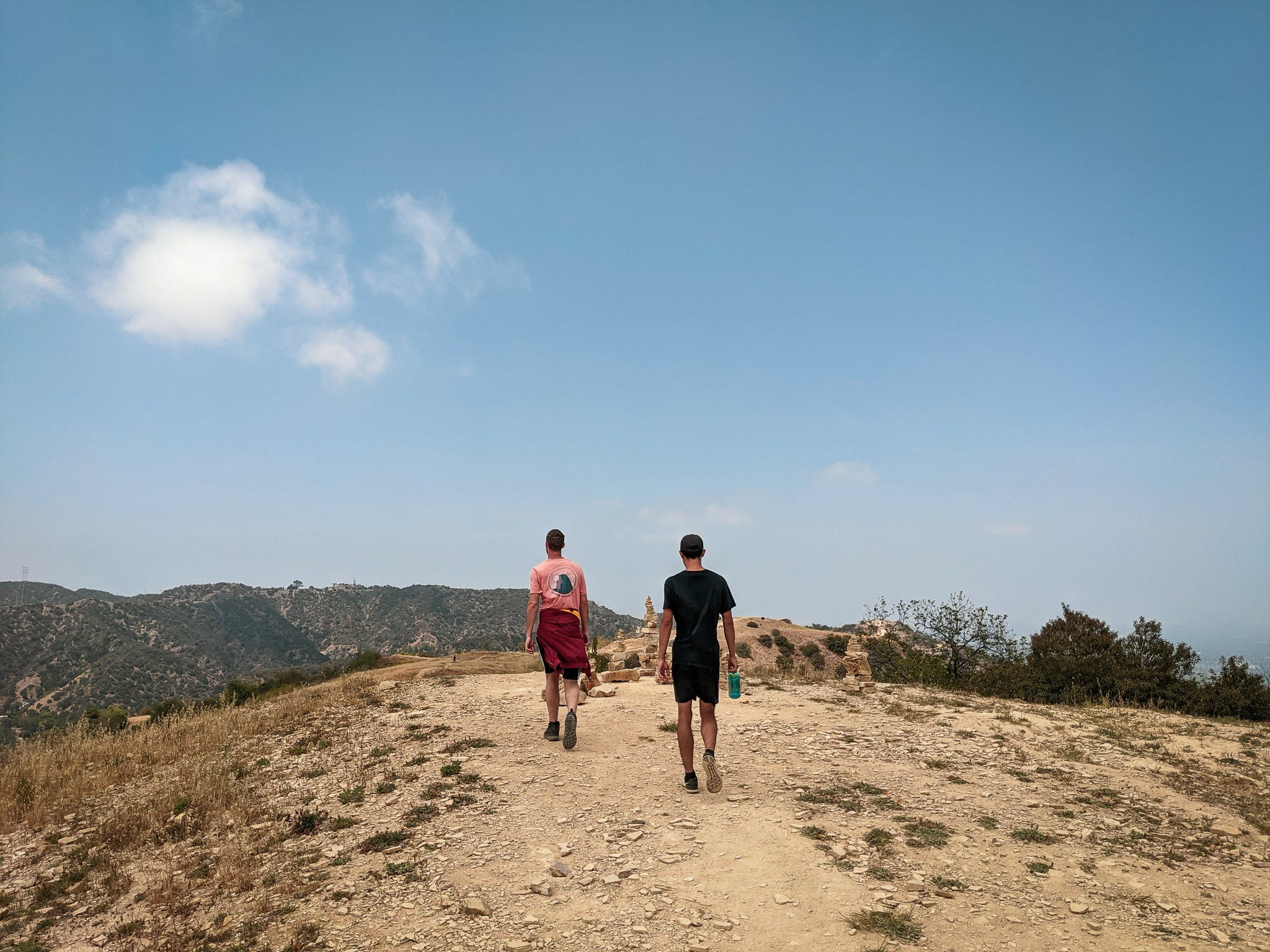 Two hikers coming to the crest of a trail at Upper and Lower Canyonback Trails in Los Angeles county