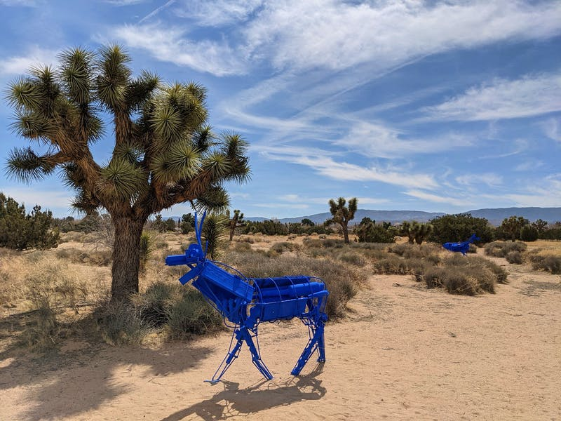 Blue art installation of deer near a Joshua Tree in the Antelope Valley