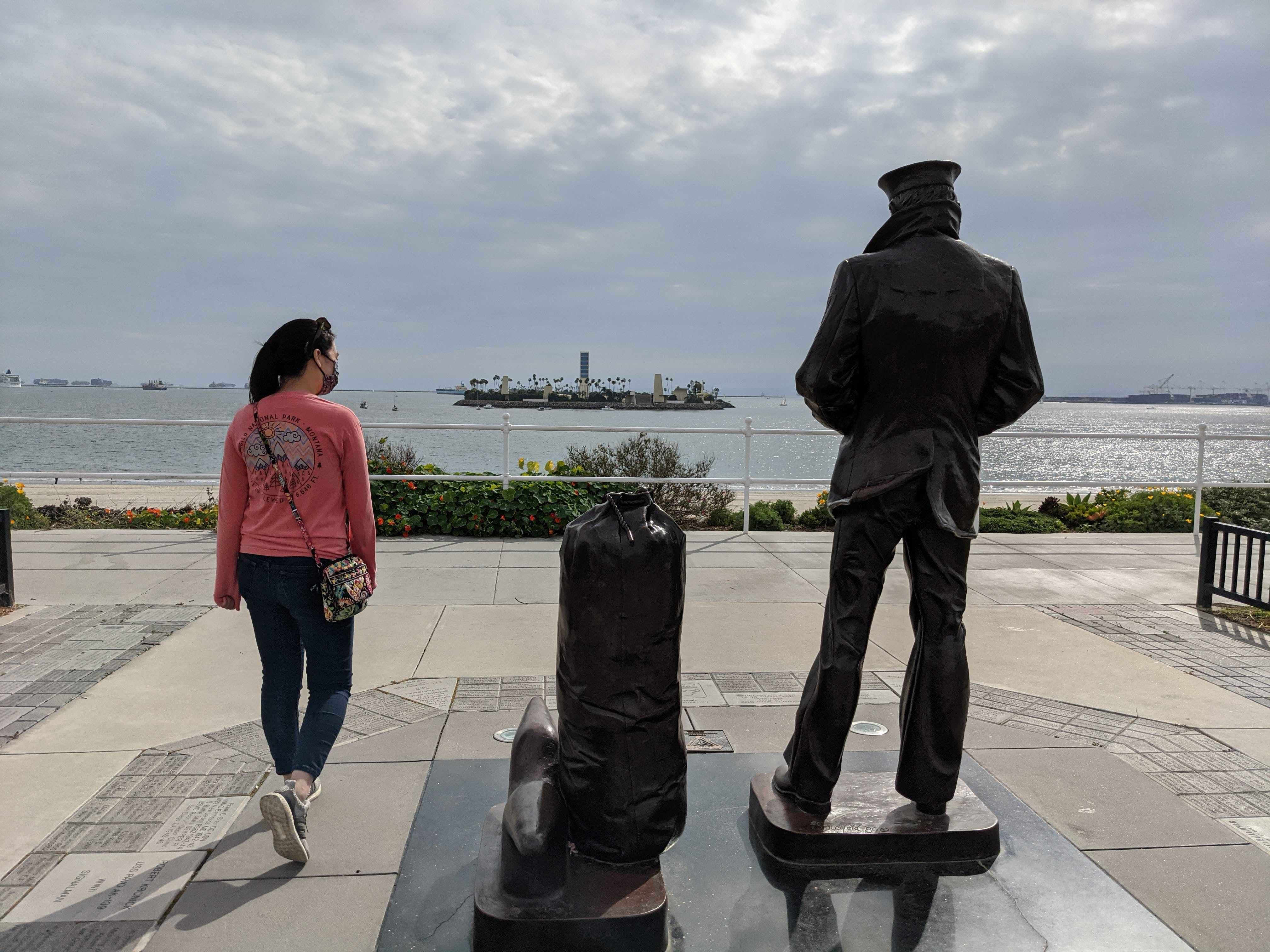 Woman standing with The Lone Sailor sculpture in Long Beach