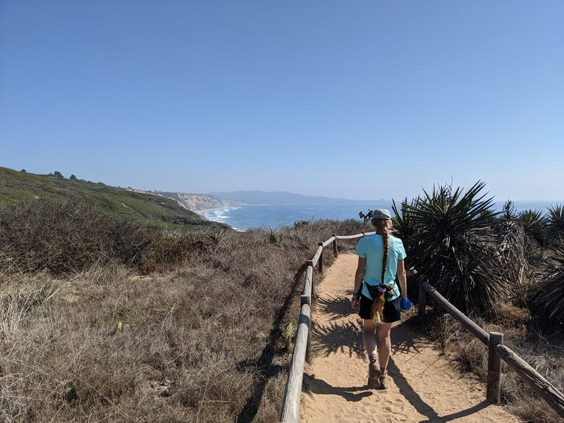 Hiker on a trail overlooking the Pacific ocean at Torrey Pines State Natural Reserve in San Diego County