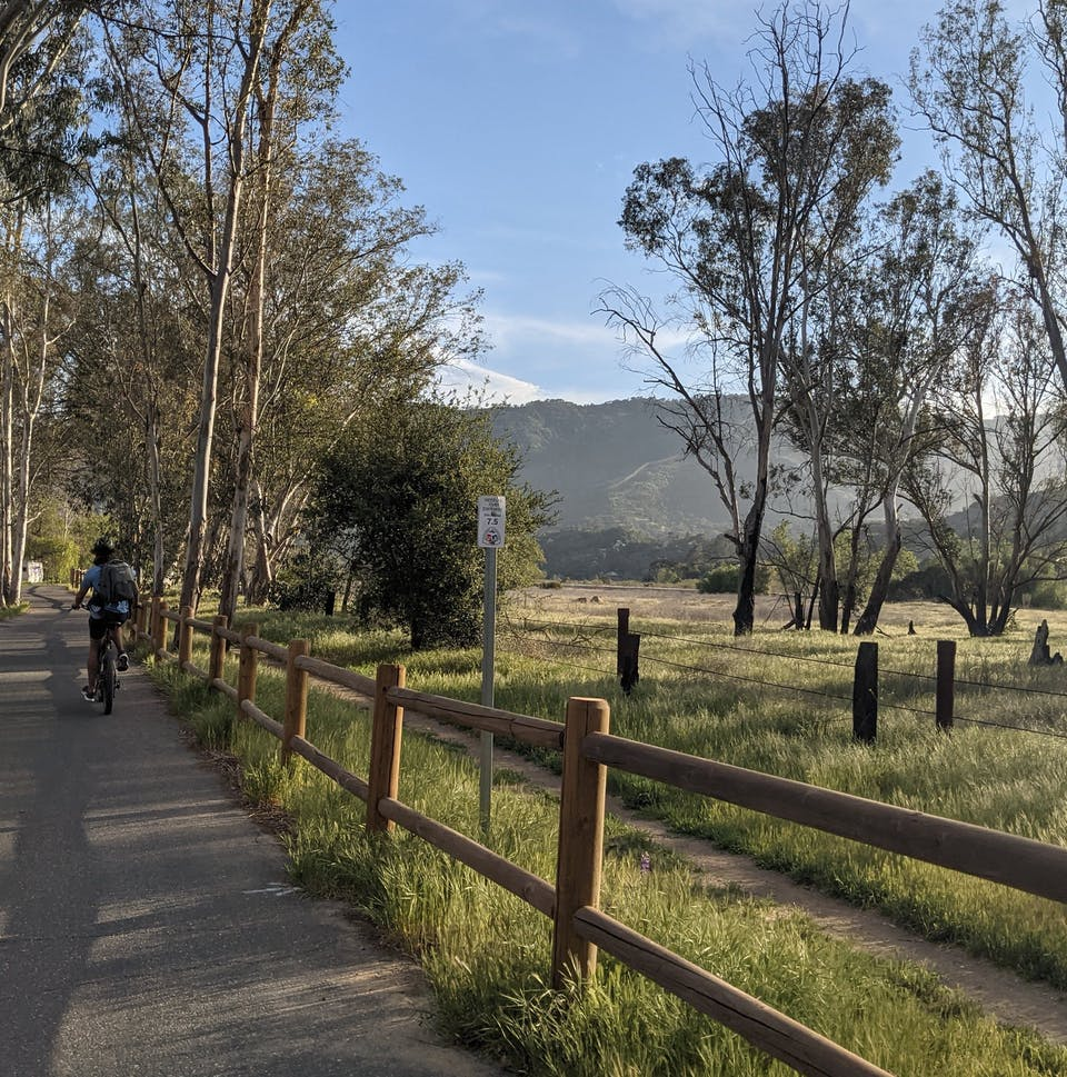 Woman bike riding next to a ranch fence and pastoral landscape with trees on the Ventura to Ojai bike trail