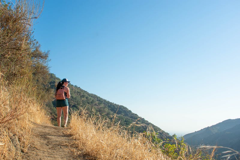 Woman hiking on the Keiser Trail overlooking a big view of the San Gabriel Mountains below in Big Dalton Canyon Wilderness in Los Angeles County