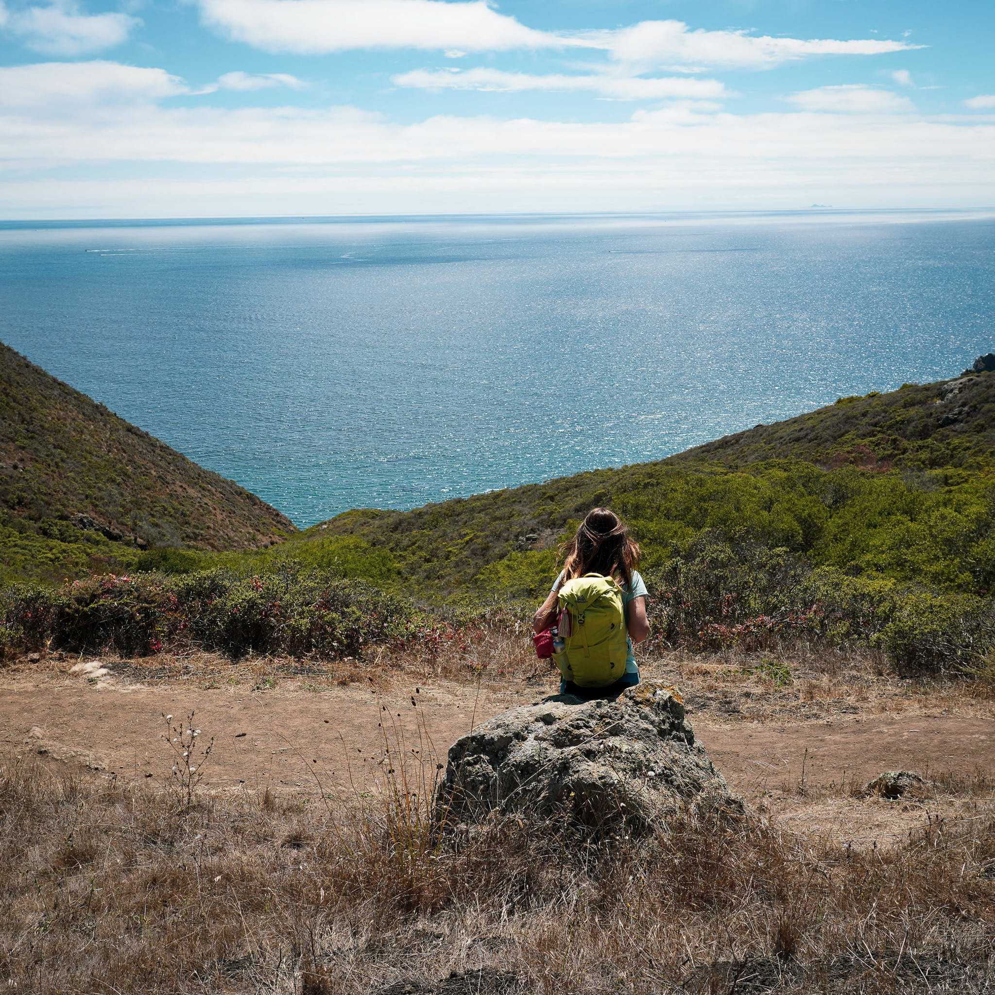 Woman resting on a rock overlooking the Pacific ocean on the Coastal Trail in the Marin Headlands