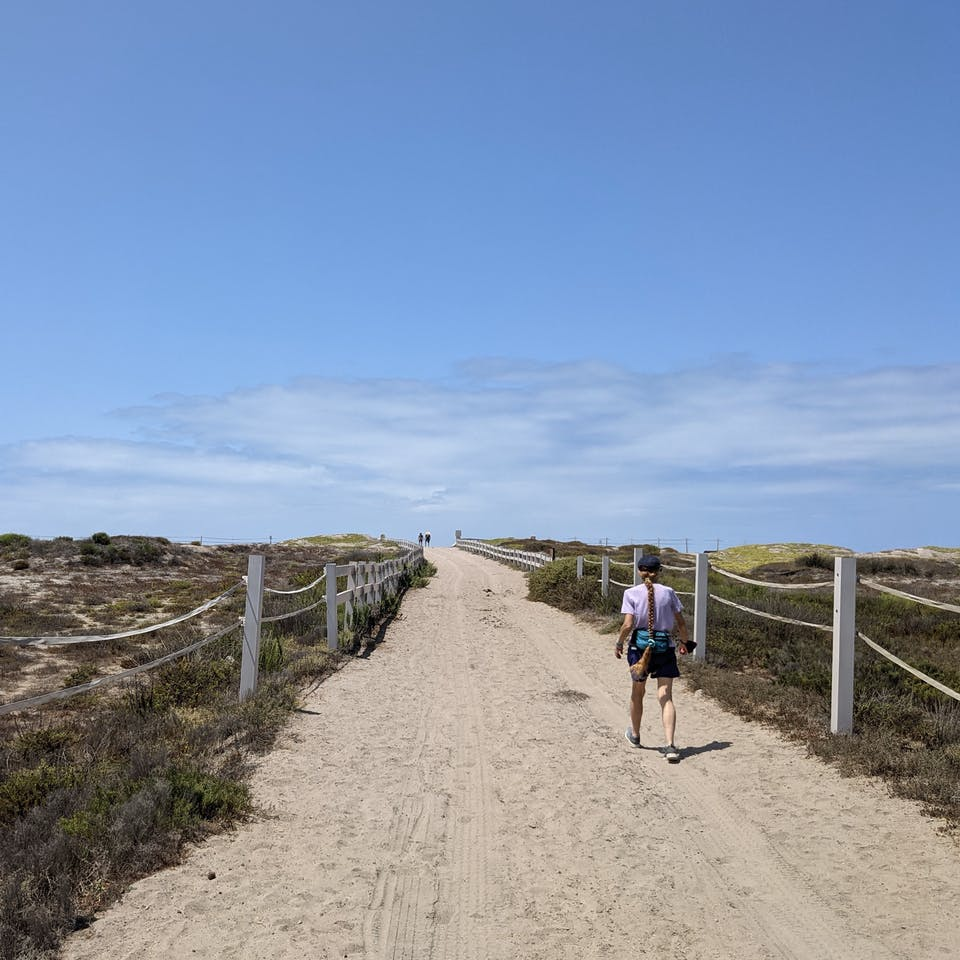 Woman hiking a wide and sandy trail at Border Field State Park in San Diego County