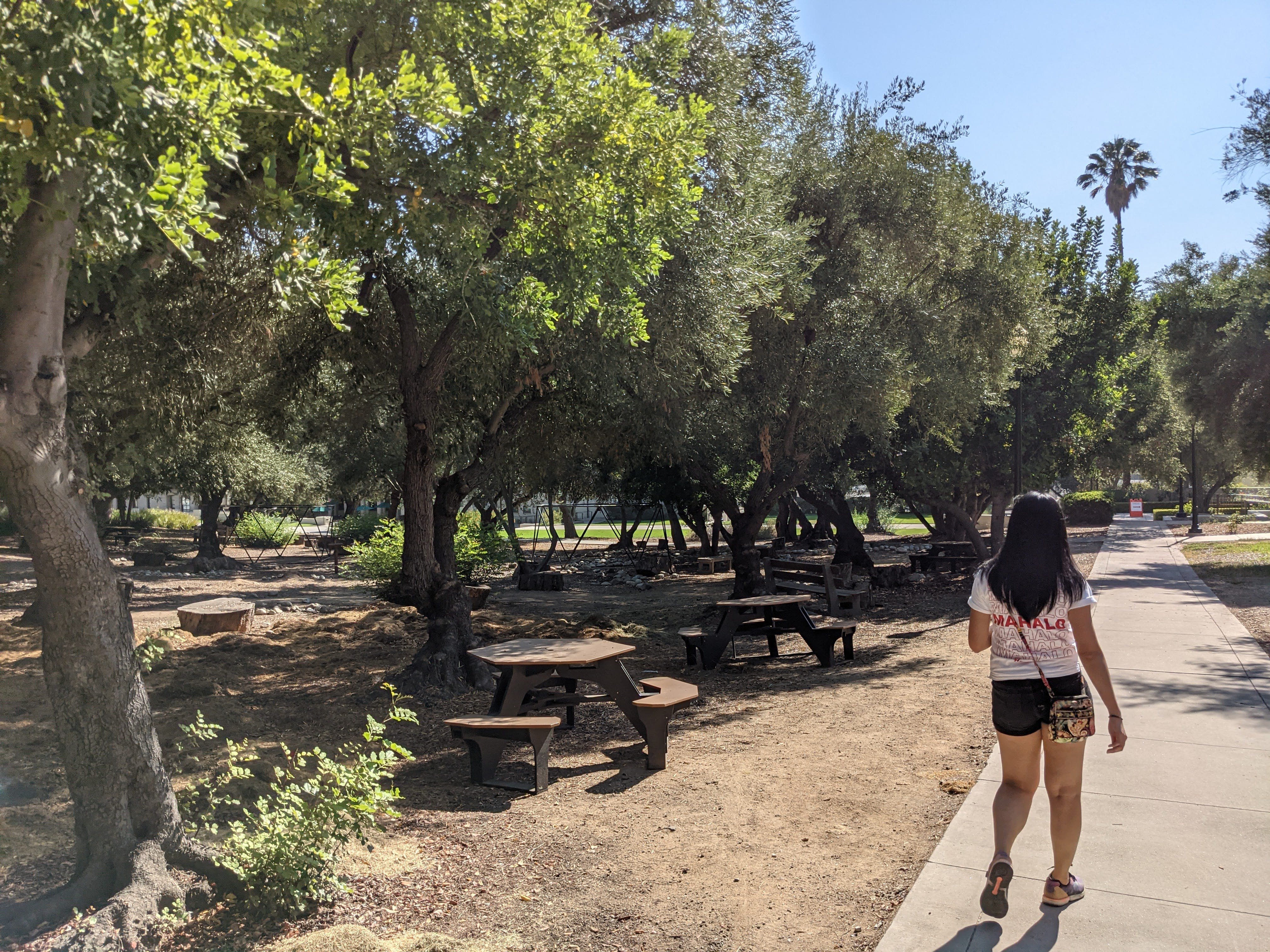 Woman walking the campus by picnic tables at Occidental Campus in Los Angeles