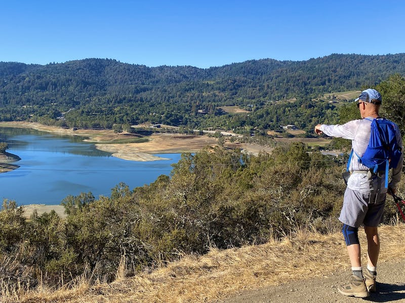 Hiker pointing towards the Lexington Reservoir at the high point of St. Joseph's Hill in Los Gatos