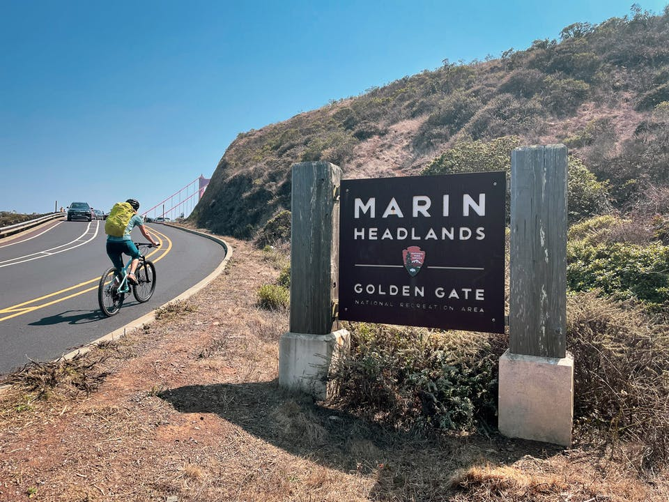 Biker passing the official sign to Marin Headlands Golden Gate in the San Francisco Bay Area