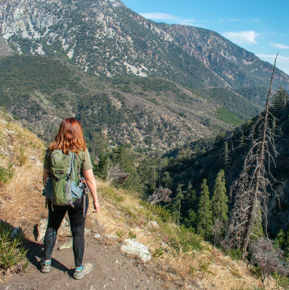 Woman stopped on a trail to look at the big mountain views from the Bear Canyon Trail in Angeles National Forest