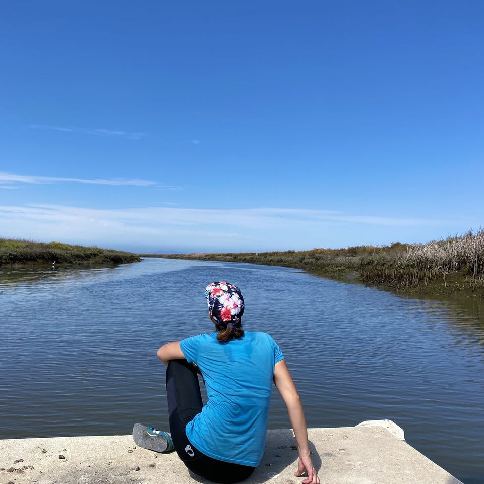 Woman sitting on a dock overlooking the water and marshland in San Jose along the Guadalupe River Trail