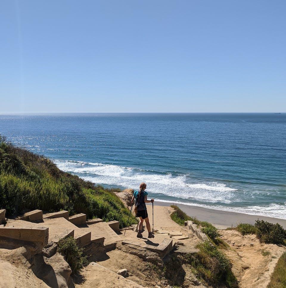 Woman hiking down to Black's Beach in La Jolla San Diego