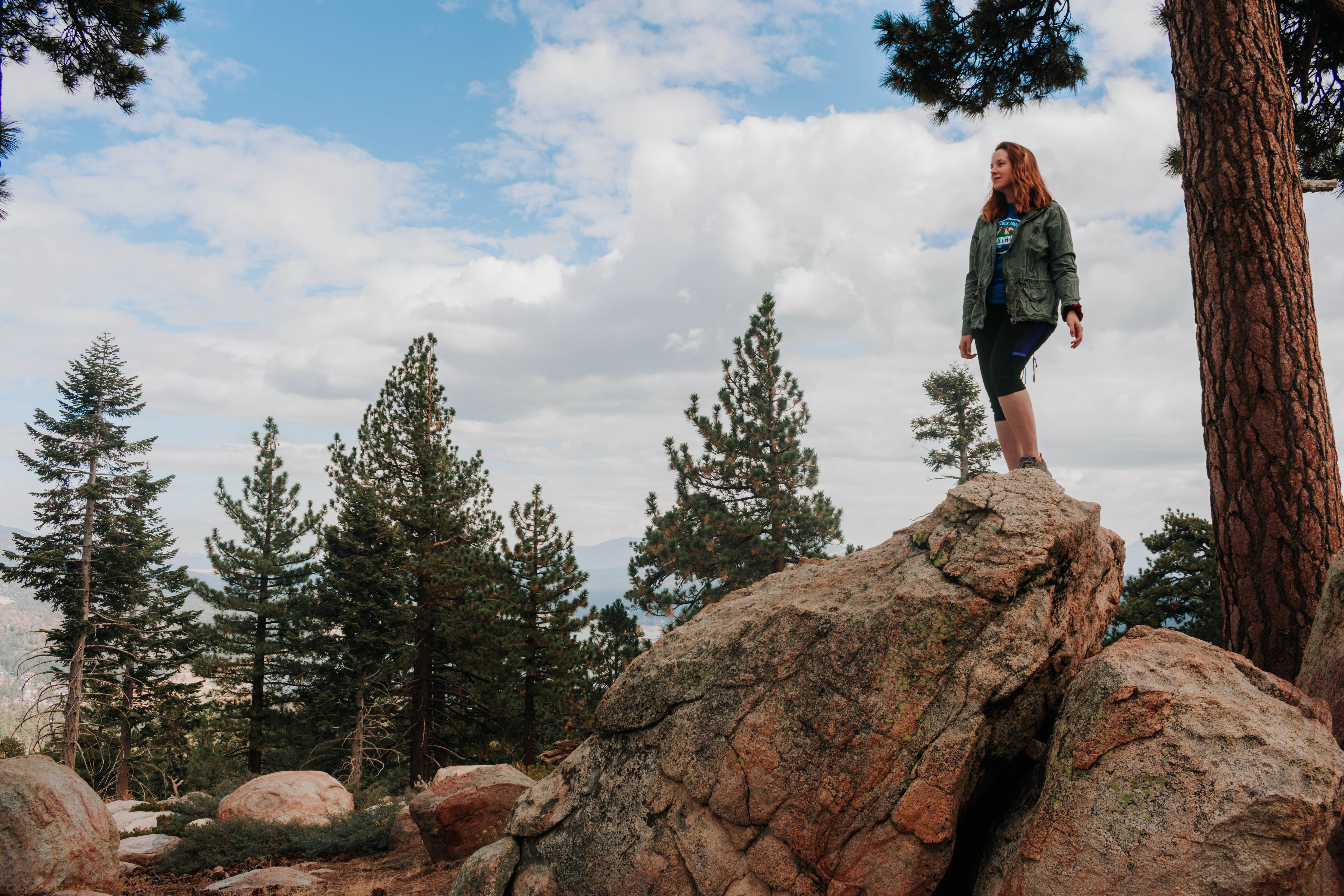 Hiker standing on a boulder surrounded by pine trees at Grays Peak in Big Bear