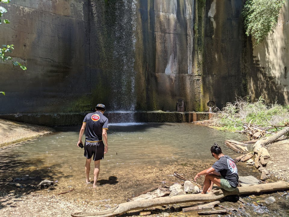 Two men wading into the water basin of historic Brown Mountain Dam in Southern California