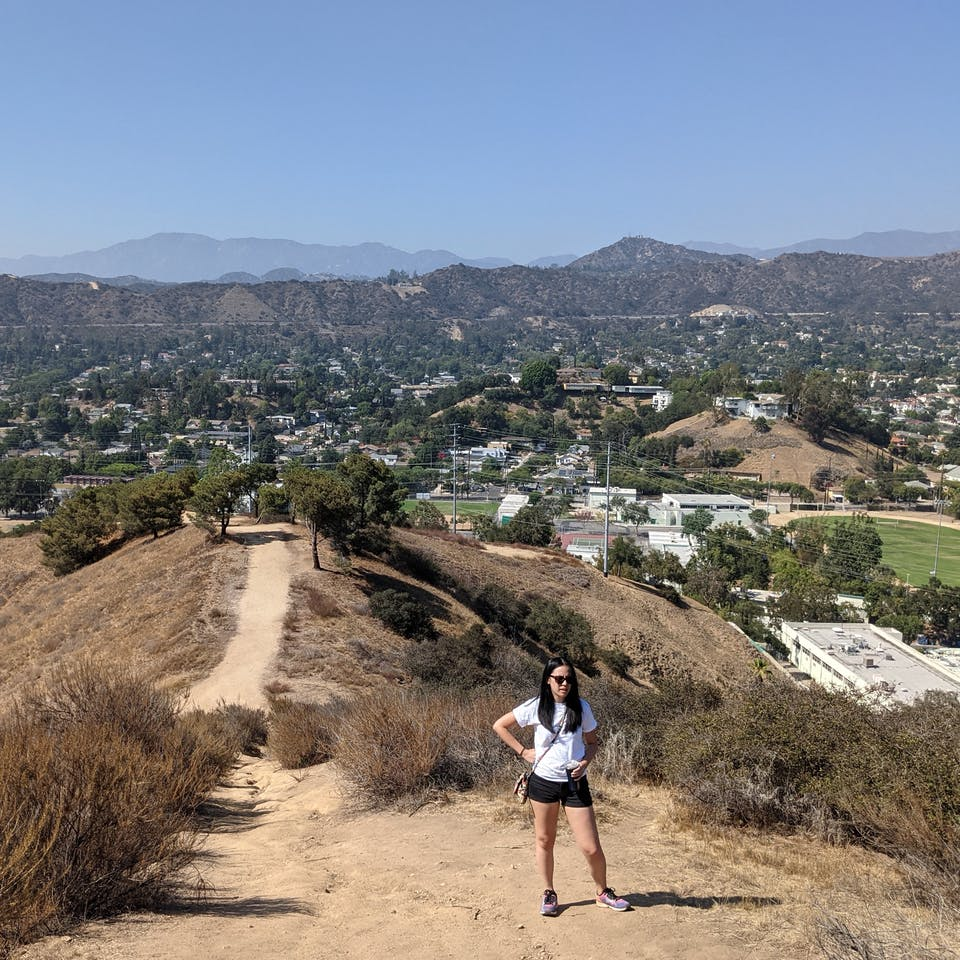 Hiker taking a break on the ascent of the trail at Fiji Hill in Los Angeles
