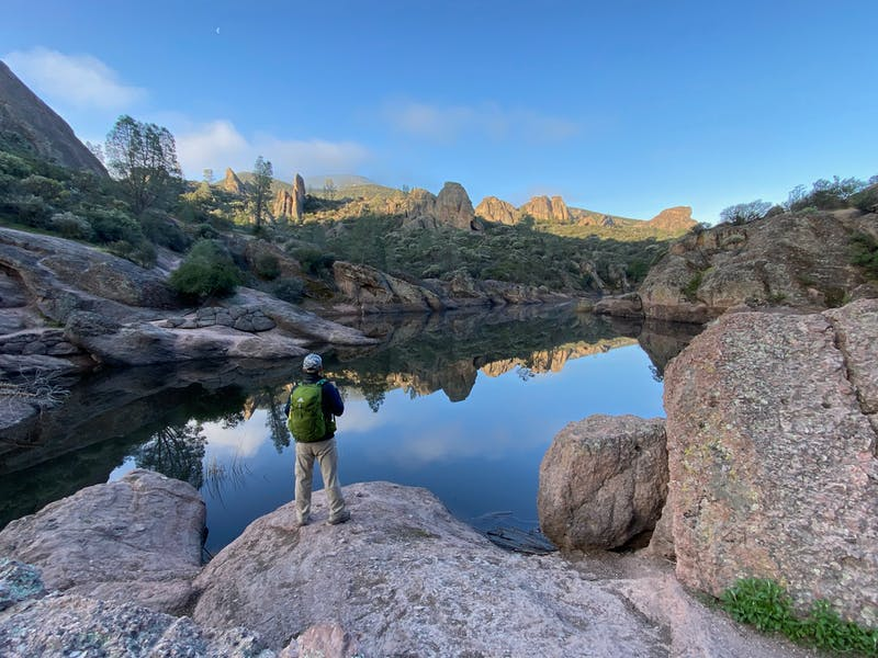 Man standing at small lake overlooking cool rock formations at Pinnacles National Park