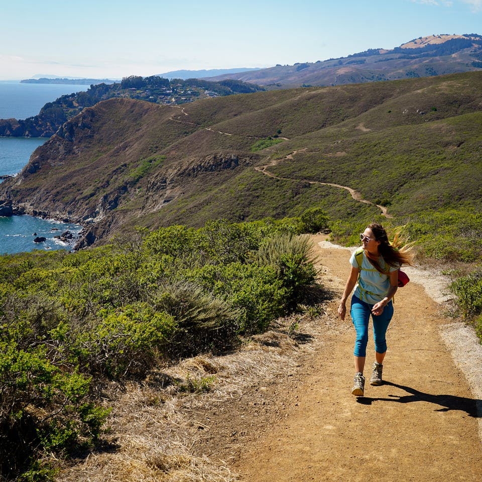 Woman hiking up the Coastal Trail next to the ocean in the Marin Headlands