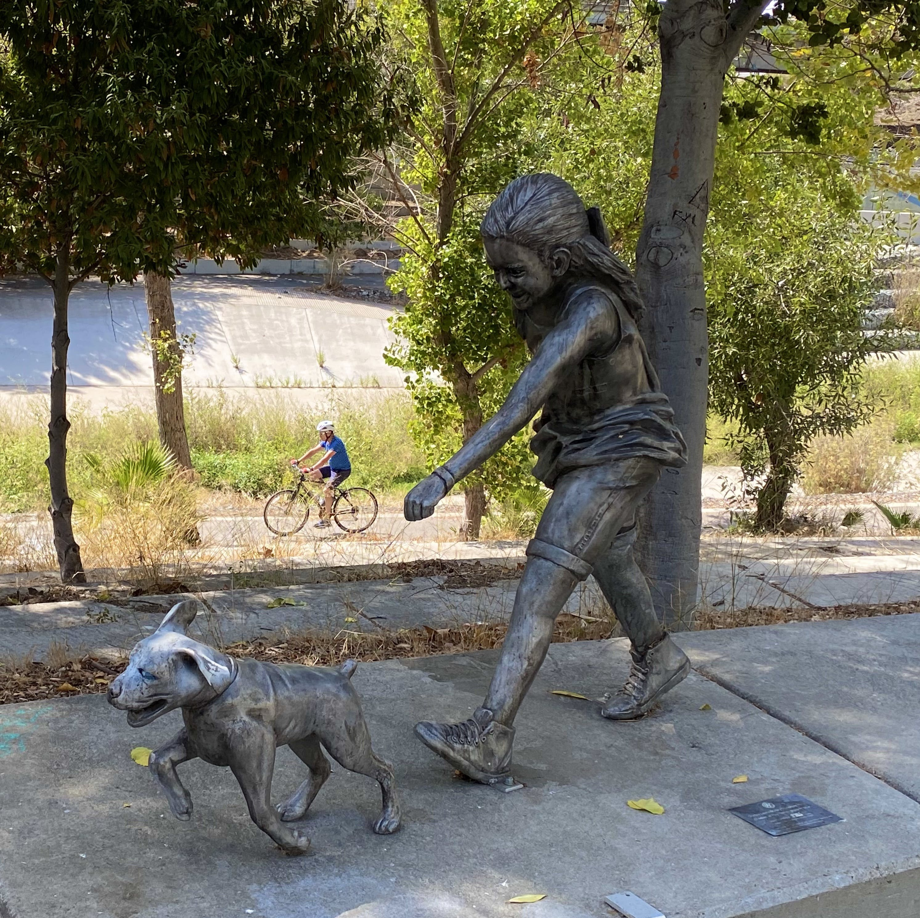 sculpture of a young girl walking her dog on a sidewalk with bike riders on the bike path below in San Jose at Guadalupe River Trail