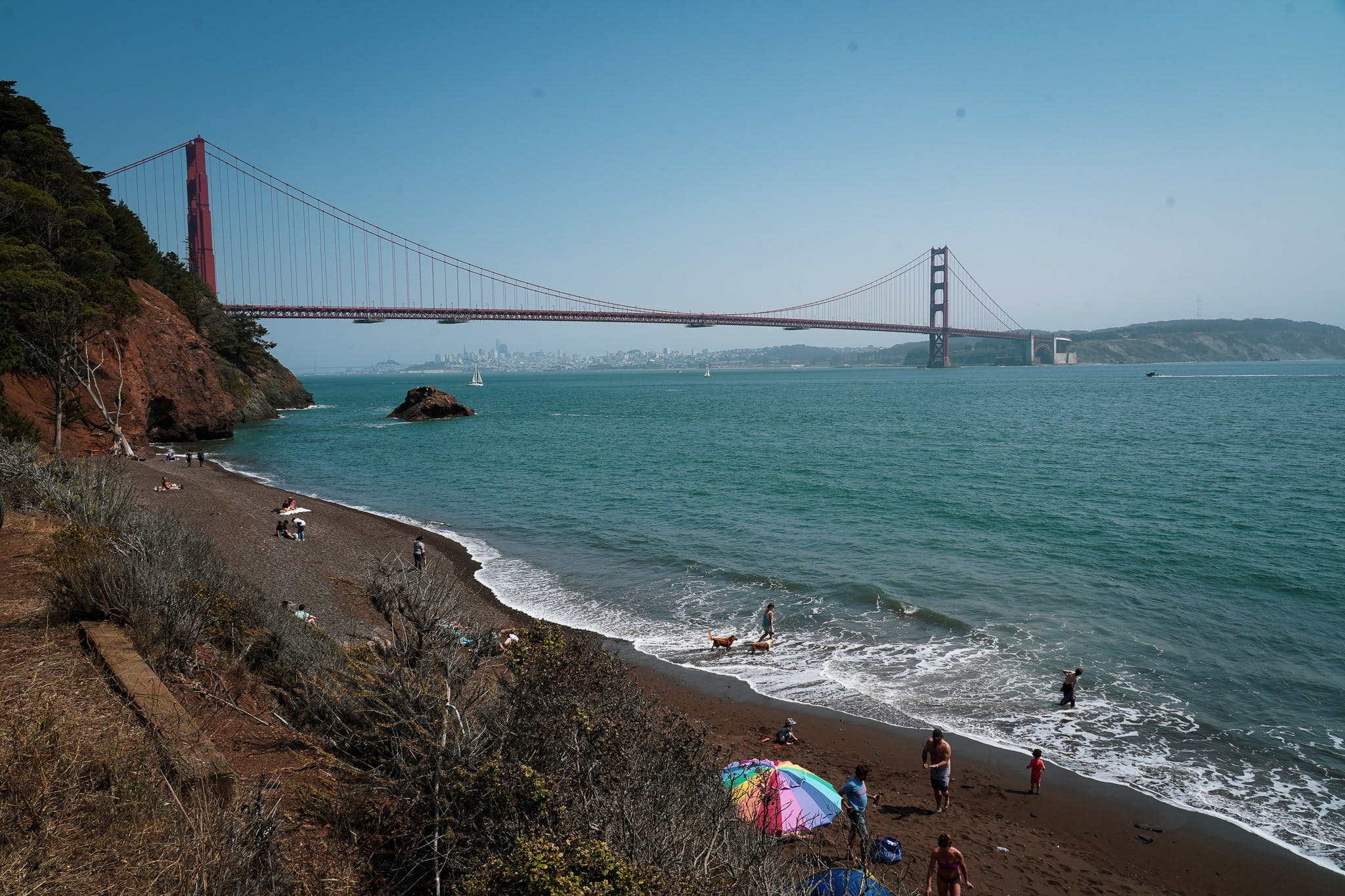 Kirby cove beach with a colorful sun umbrella and people on the beach with the Golden Gate Bridge in the background