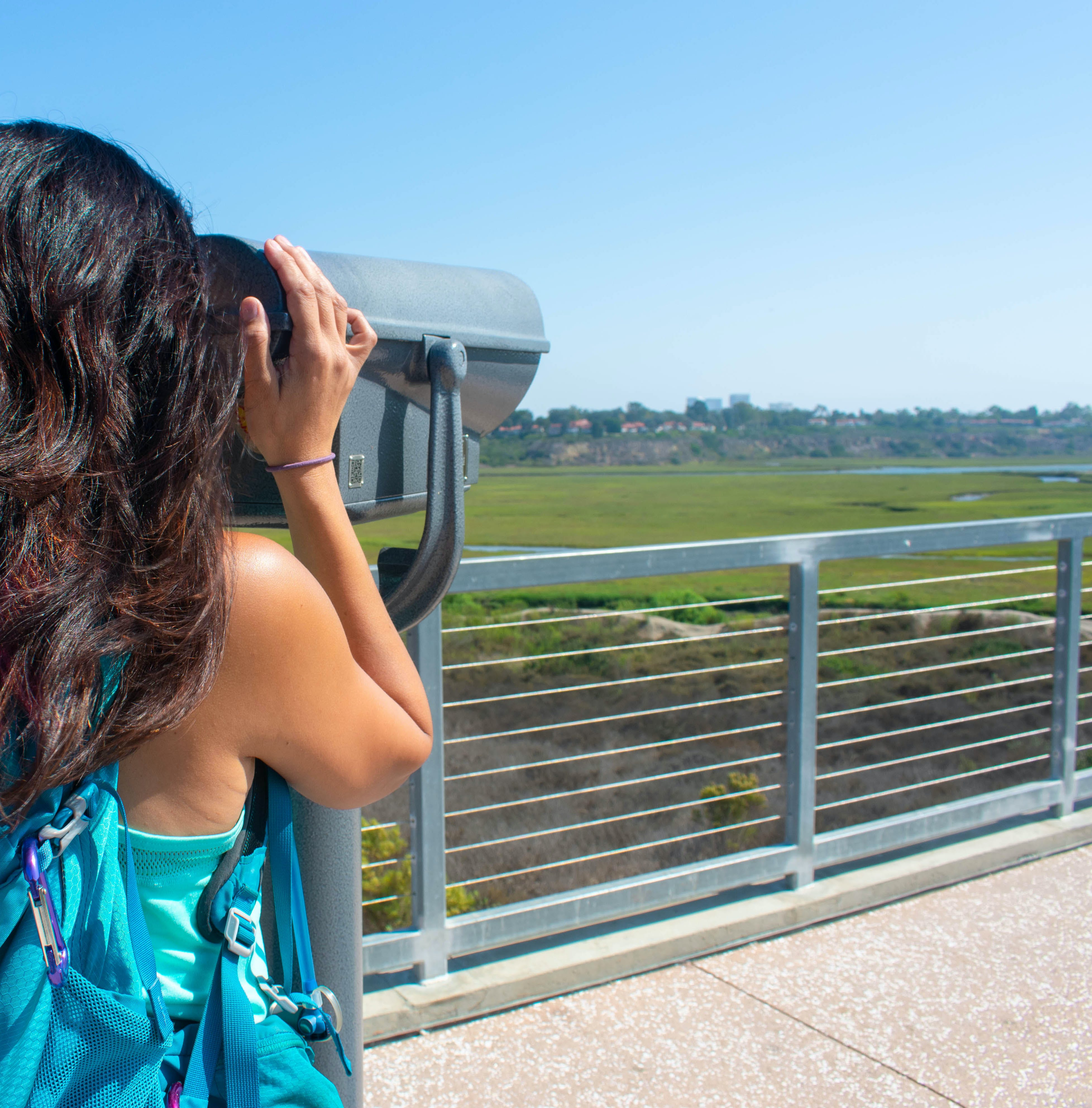 A woman looks through a telescope out towards Upper Newport Bay Nature Preserve in Orange County
