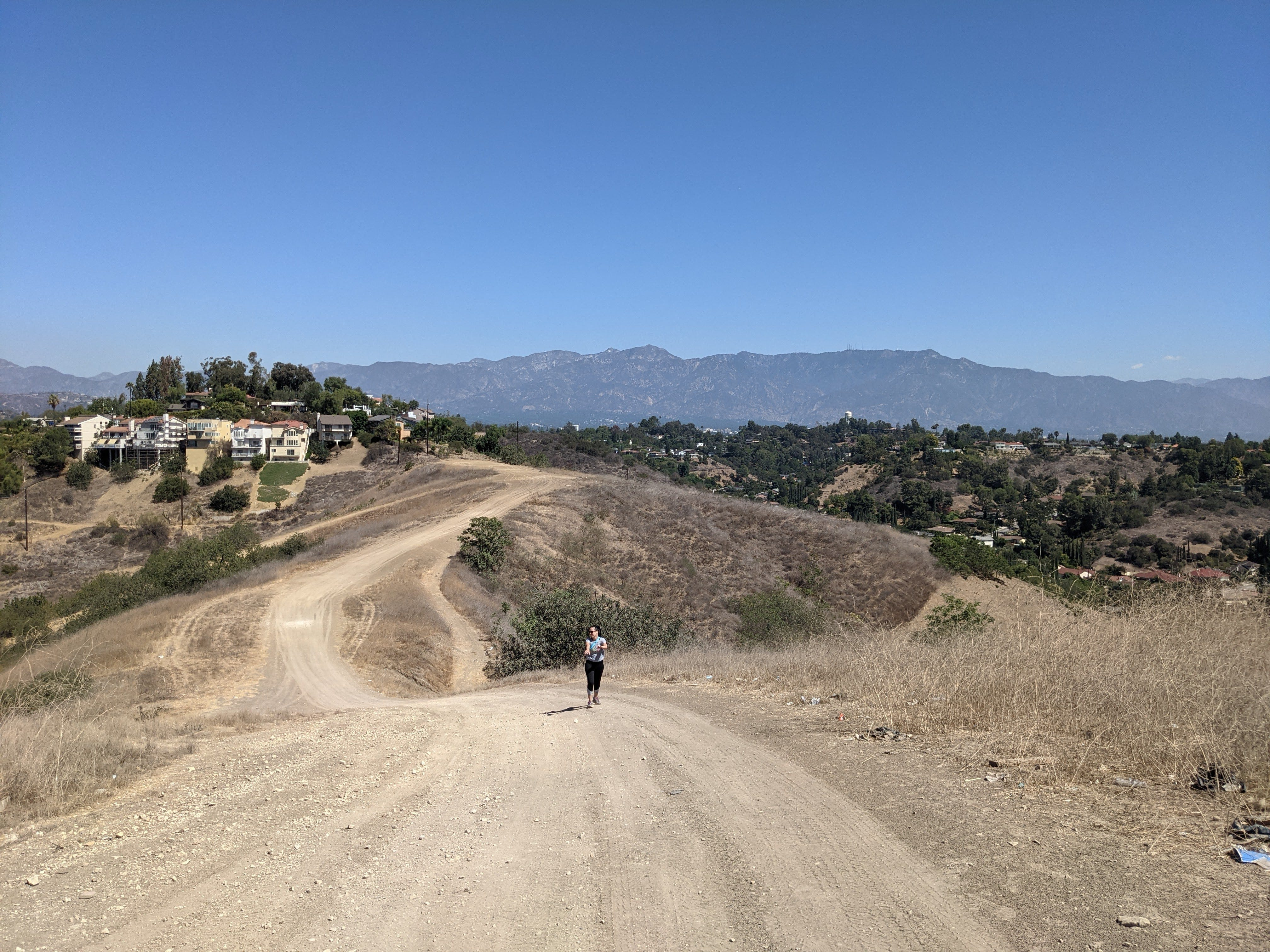Hiker on wide open rolling trail at Elephant Hill Open Space in Los Angeles