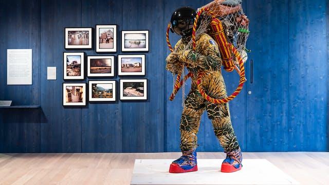 展览画廊空间的照片,有一个蓝色污迹木墙壁在背景中,在它垂悬的9张照片被淹没的景观。在前景中是一个类似宇航员的人物的寿命艺术品。携带一个包含行李箱的大型网,包括行李箱。