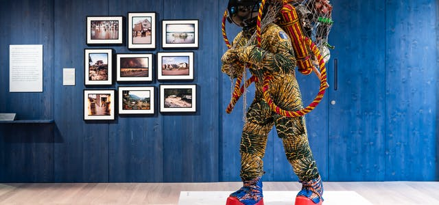 Photograph of an exhibition gallery space, with a blue stained wood wall in the background, on which are hung 9 photographs showing flooded landscapes. In the foreground is a life-size artwork of a figure resembling an astronaut. carrying a large net containing assorted objects including a suitcase.