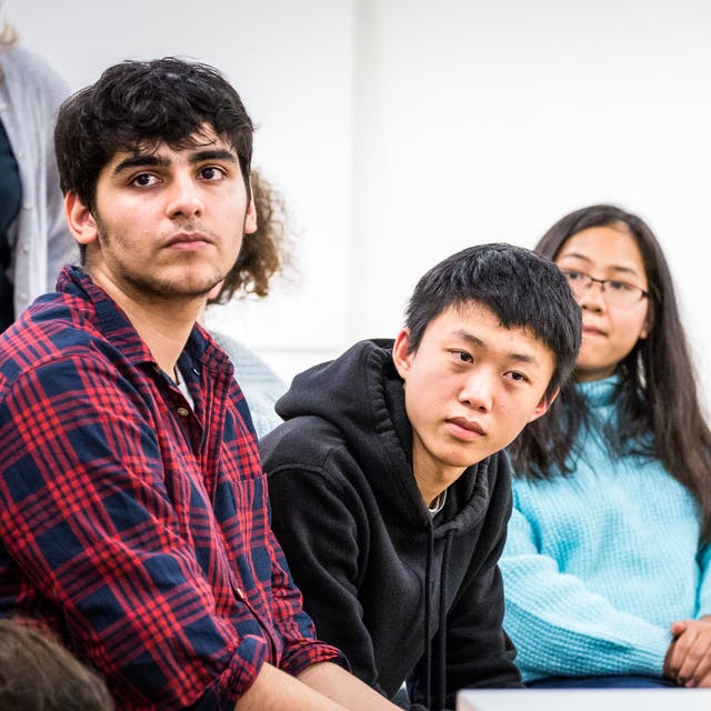 Photograph of a group of young people listening to a presenter who is stood