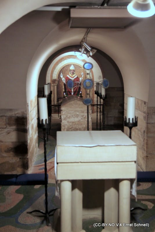 The photo shows the sarcophagus of Archbishop St. William Fitzherbert of York between an altar and a mural of his image in the crypt of York Minster.