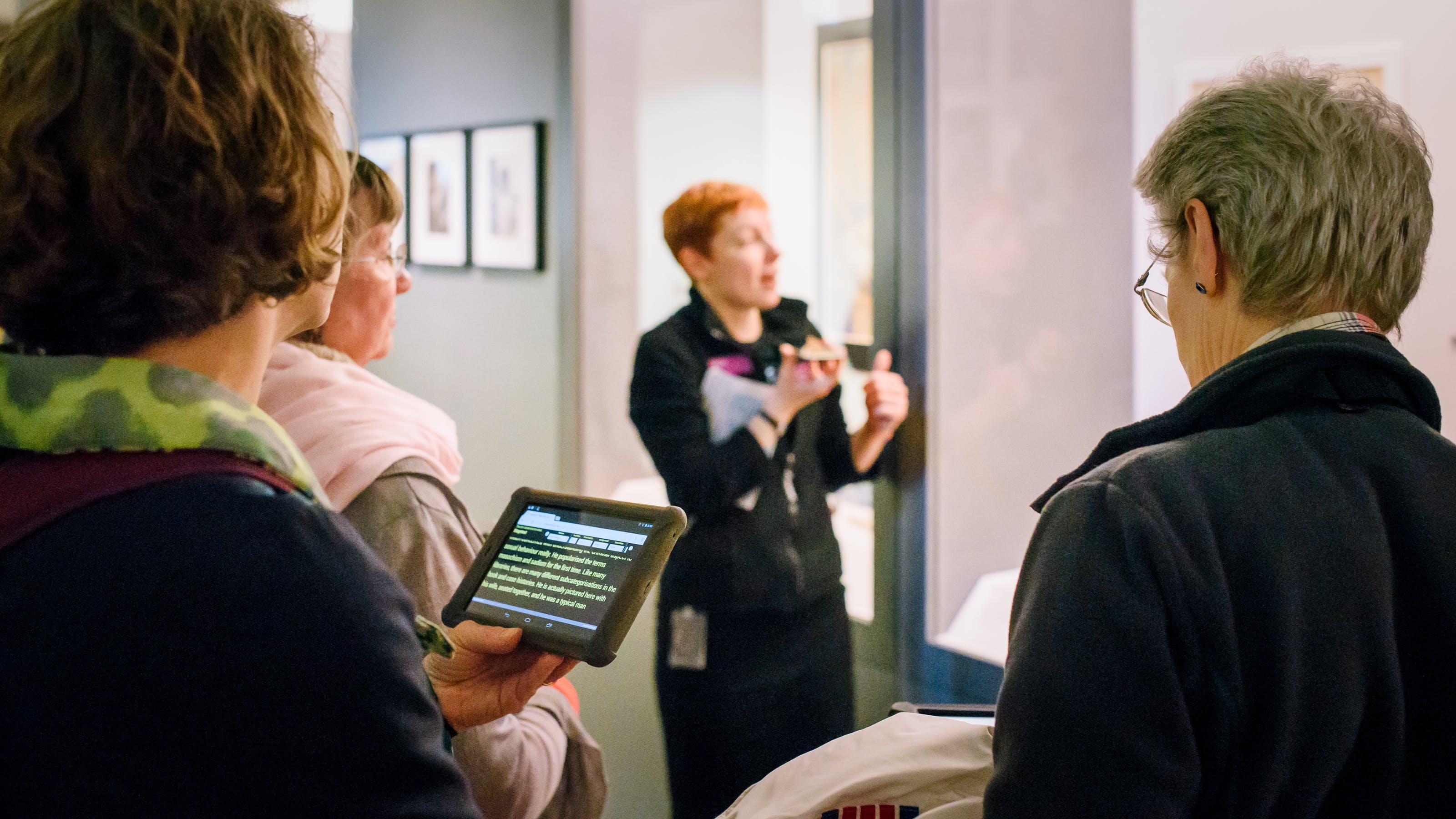 Photograph of a Wellcome Visitor Experience Assistant speaking into a phone whilst giving a speech-to-text tour of a gallery. In the foreground is a tablet displaying the transition.