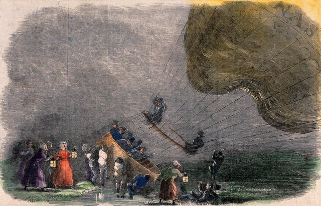 A hot-air balloon has landed in stormy weather, a crowd of people have brought lamps and are helping the aeronauts.