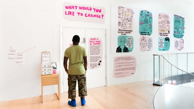 Photograph of a man looking at an exhibition installation on a gallery hoarding, made up of hand drawn text and illustration. The large pink title reads,