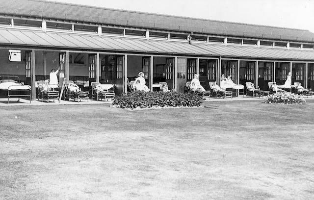 Shows patients and staff at a sanatoria in the West Midlands. Patients are sat outdoors, while accompanied by staff.