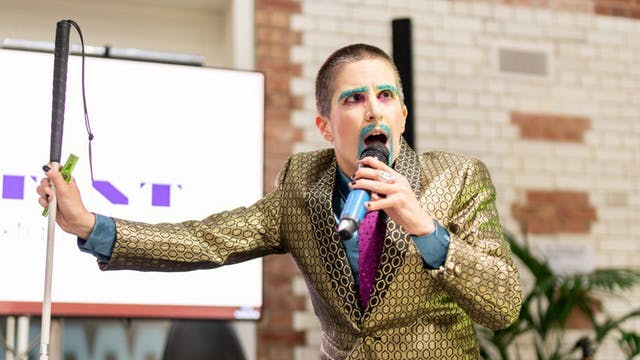 Amelia Cavallo AKA Tito Bone performing with a microphone and a white cane, wearing glittery make-up and beard in a gold suit