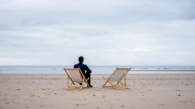 Photograph of a young man sat in a deck chair on a sandy beach, looking out to sea. To his right is an empty deck chair.
