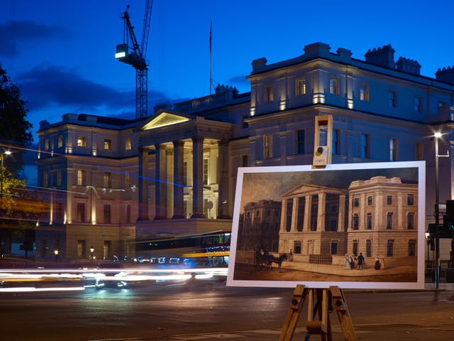 Photograph of the former St George's Hospital with an historical image of the hospital displayed in front of it on a wooden artist