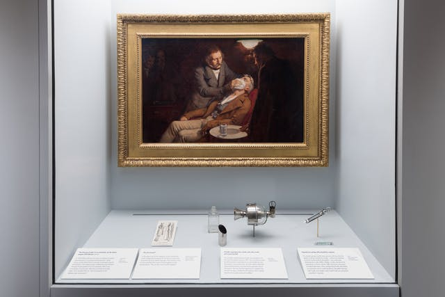 Photograph of an oil painting on display in the Teeth exhibition at Wellcome collection. The oil painting shows a dentist anaesthetising a patient by placing a cloth soaked in ether over his mouth.