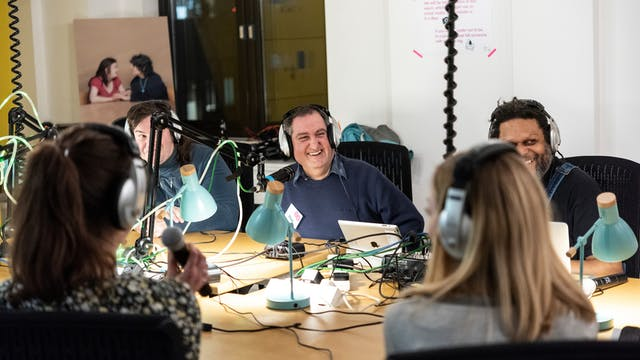 A group of people smiling and talking at a live radio session sitting around a table with microphones on the table in front of them and headphones on.