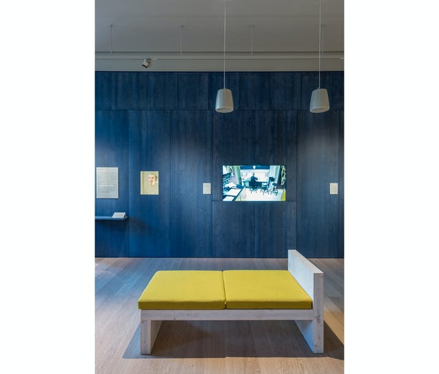A photograph showing a wooden bench with yellow cushions in front of a large tv screen embedded in a dark blue wood panelled wall with two speakers hanging on long cords from the ceiling.