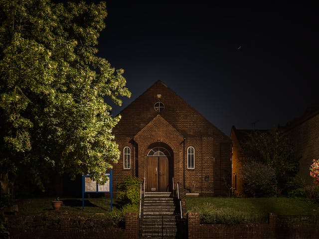 Photograph of Eltham Spiritualist Church at night. The two-storey building is set back from a main road, with a lawn and a brick wall fence.  The facade has three windows, two on the ground floor and one small circular window in the apex of the roof.