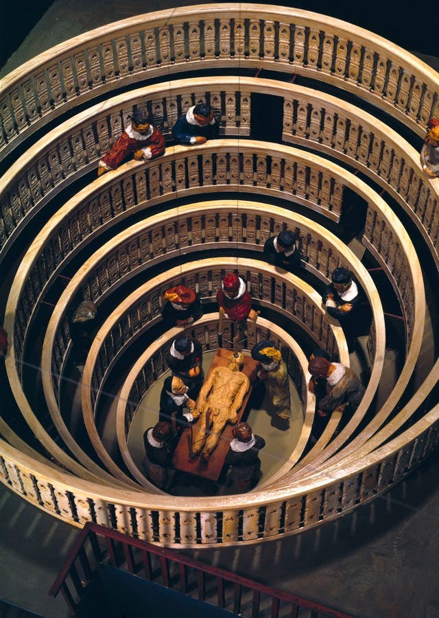 Image of round anatomy theatre model with people around a body