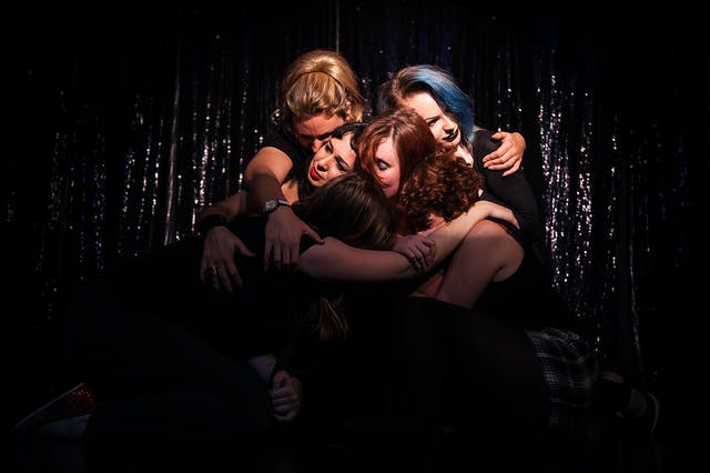 A coloured photograph group of several women with their arms around each other hugging, on a black background.