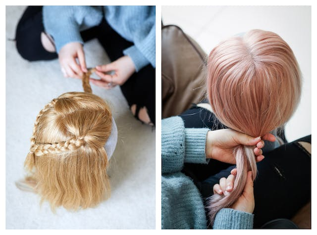 Photographic diptych. Both images are similar in that they both show a view from above looking down on a wig resting on a mannequin head. In both images there is the lap and hands of a young girl who is in the process of caring for the wigs. The main difference is that the image on the left shows a blonde wig with plaits and the image on the right show a light pink straight haired wig.