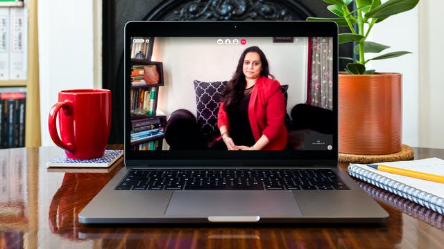 Sonia Wigh on a video call. Sonia is appearing on the laptop screen. On the desk around the laptop, there is a red mug, a small house plant and pen, and paper.