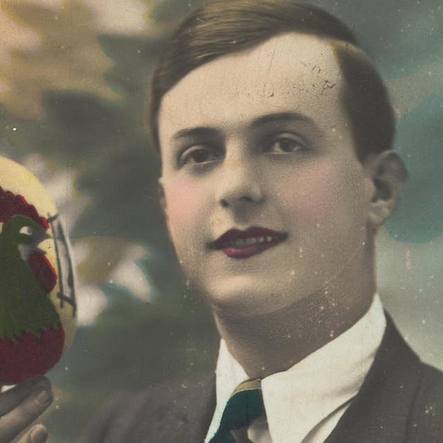 Colourised photograph of a young man holding an easter egg with a picture of a cockeral on it.