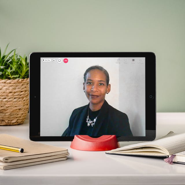 Photograph of a laptop on a desk, on the screen is a photographic portrait of Dr Rana Hogarth. Around the laptop is an open notebook and pen, a pile of notebooks and some house plants.