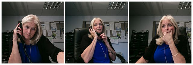 Photographic triptych showing the same woman in each image, sat in an office environment. In the left hand image the woman holds a landline telephone receiver to her right ear. She is looking down off to camera right. In the middle image she holds the receiver to her right ear and she is looking away to camera left, mid sentence. Both hands hold the receiver. In the right hand image she is not holding the receiver but has her left hand supporting her chin and appears to be looking into a screen off to camera right.