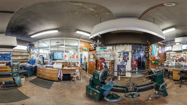 A distorted fish-eye photograph of a workshop with various machinery and posters.
